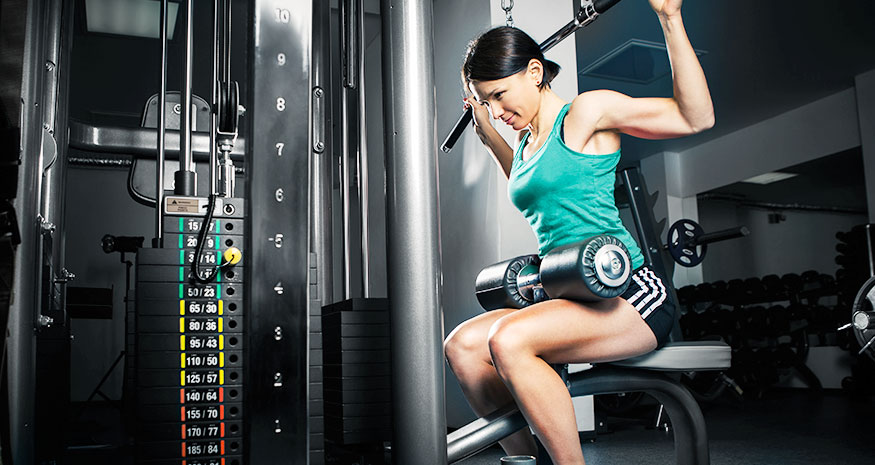 Woman doing lat pulldowns behind her neck at gym