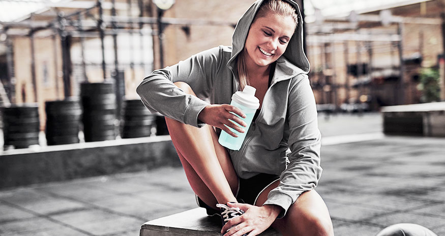 Woman drinking while resting at gym