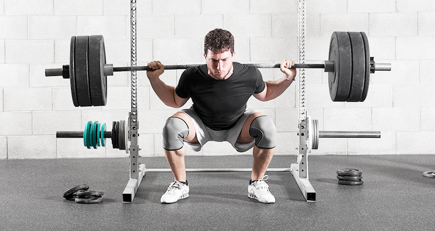 Man squatting at gym in front of squat rack