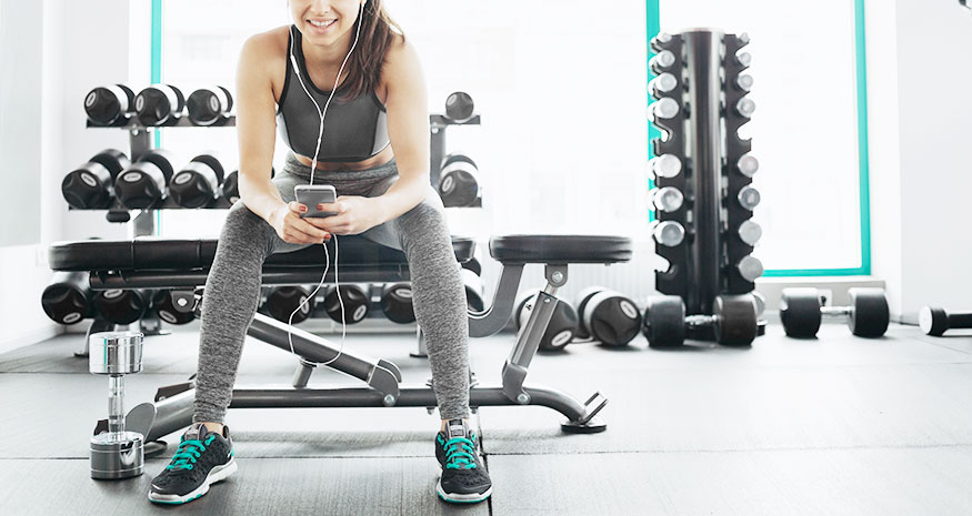 Woman sitting on bench and on phone while resting at gym