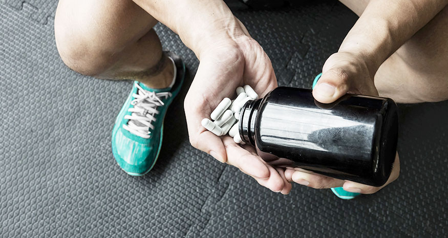 Man pouring supplement tablets into hand while at gym