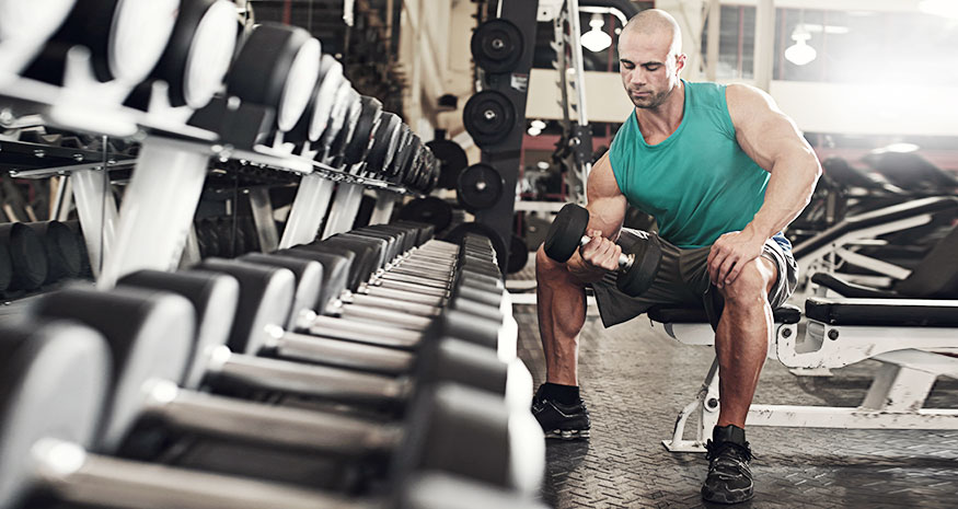 Man doing concentration curls in front of dumbbell rack