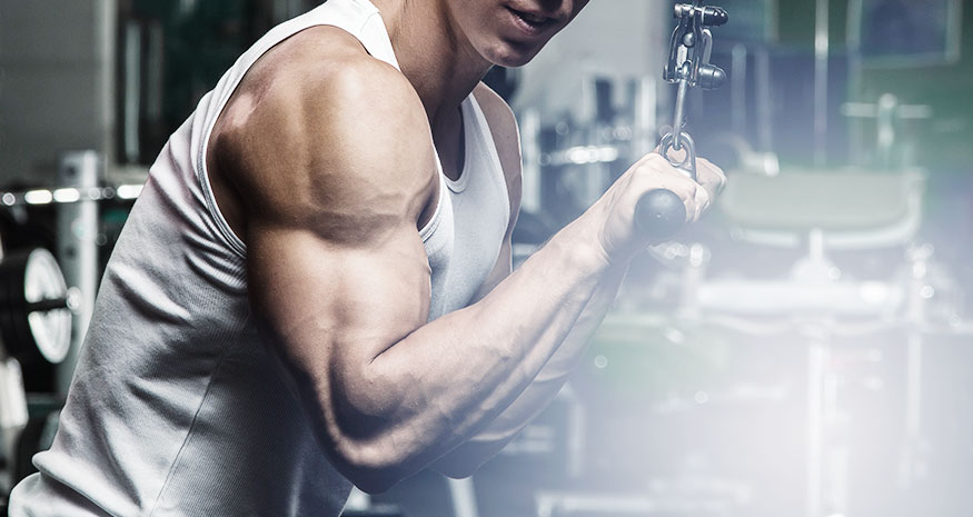 Fit man doing cable tricep extensions