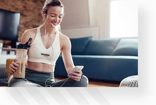 Young female on phone during rest while working out at home, drinking protein shake