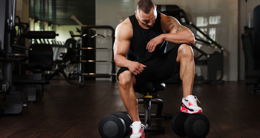 Man sitting on bench and stepping on dumbbells in gym