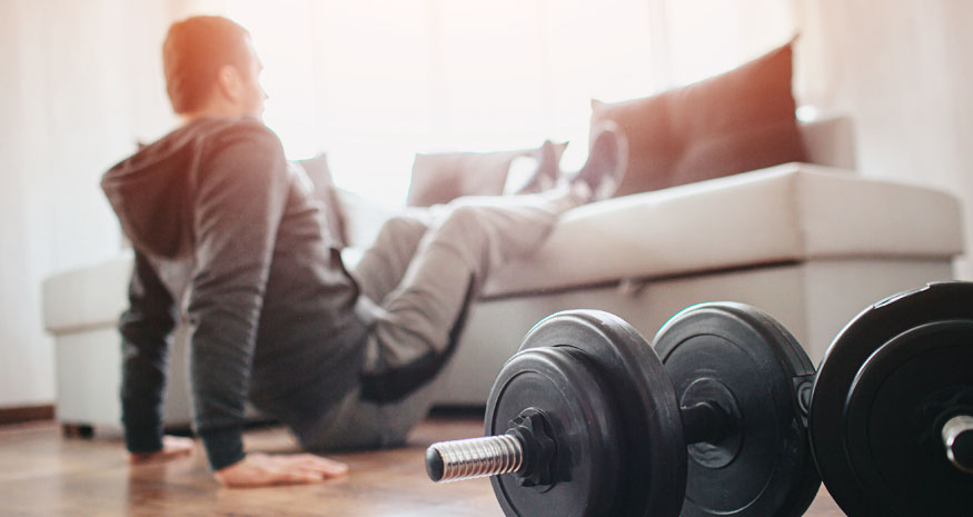 Man working out at home on couch with dumbbells